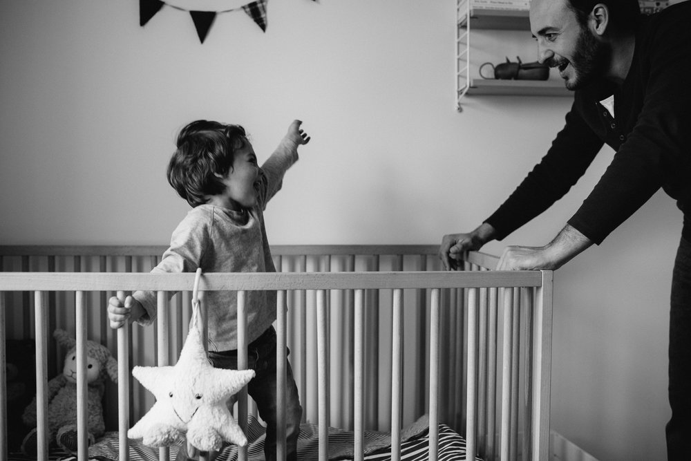 2 year old toddler boy playing and laughing in crib - stouffville in-home family photography