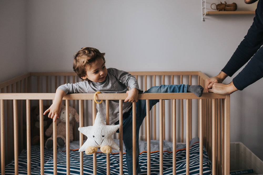 2 year old toddler boy trying to climb out of crib - newmarket in-home family photography