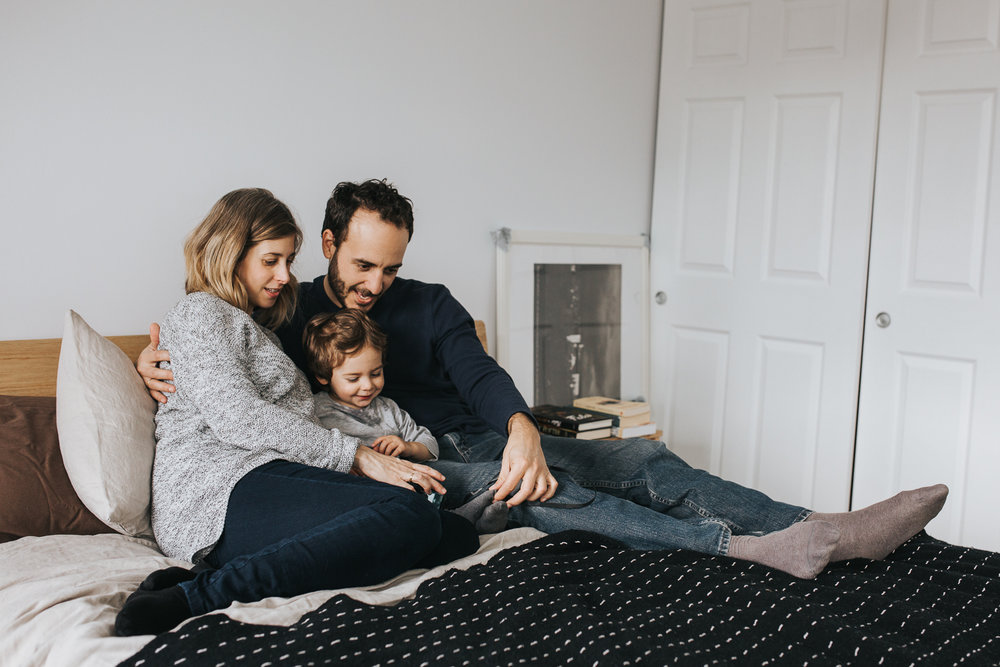 family of 3 with 2 year old toddler boy and pregnant mother snuggle on bed - stouffville in-home family photography