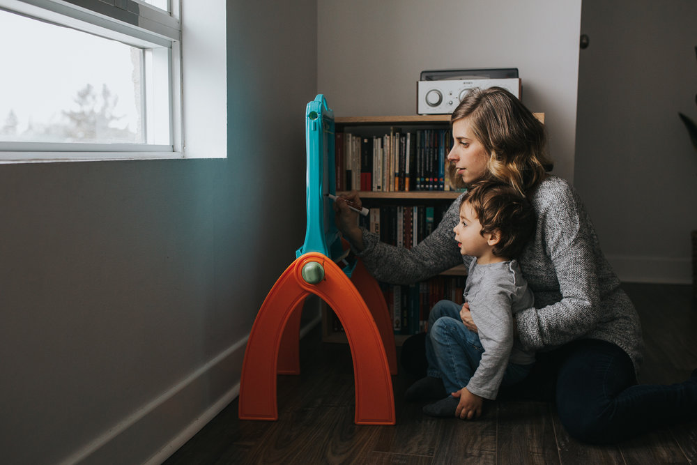 pregnant mom with short blonde hair helps 2 year old toddler son draw on easel - uxbridge in-home family photography
