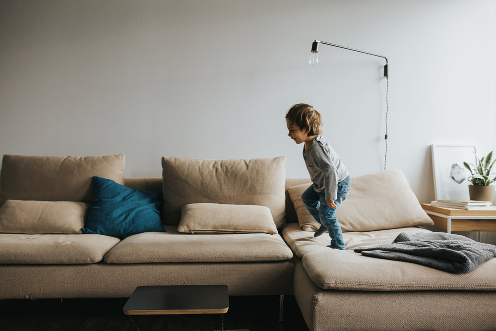 2 year old brunette toddler boy runs across sectional couch - markham in-home family photos