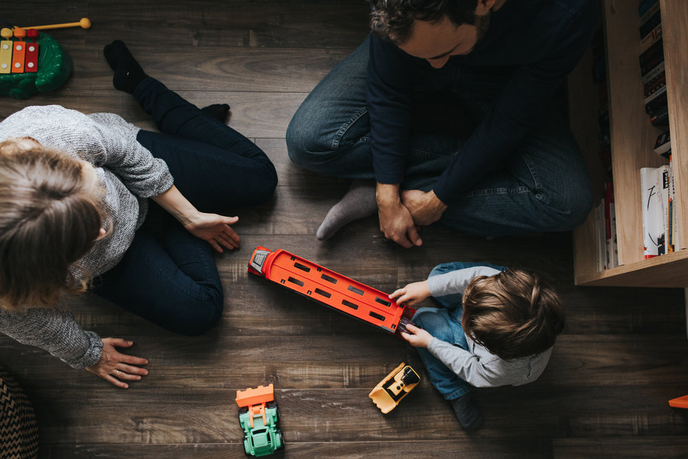 family of 3 with 2 year old toddler boy playing with trucks on floor - newmarket in-home family photos