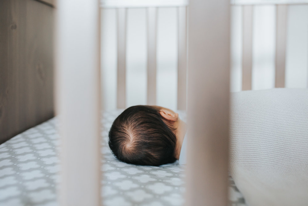2 week old baby boy with dark hair sleeping in nursery crib - Markham lifestyle photos