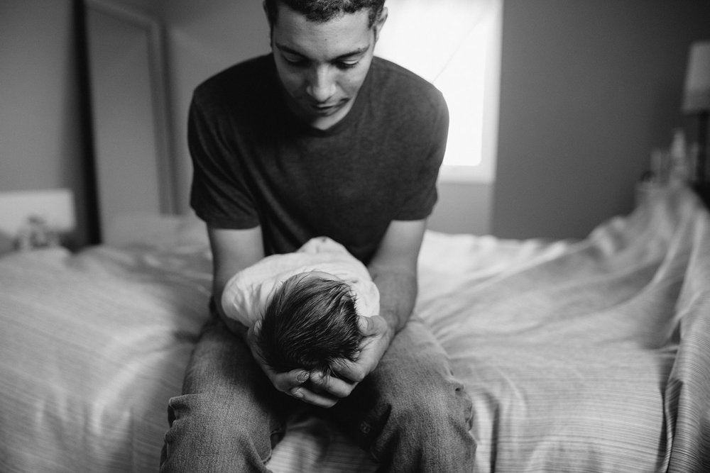 new dad holding and looking at 2 week old baby girl - Markham lifestyle photography session