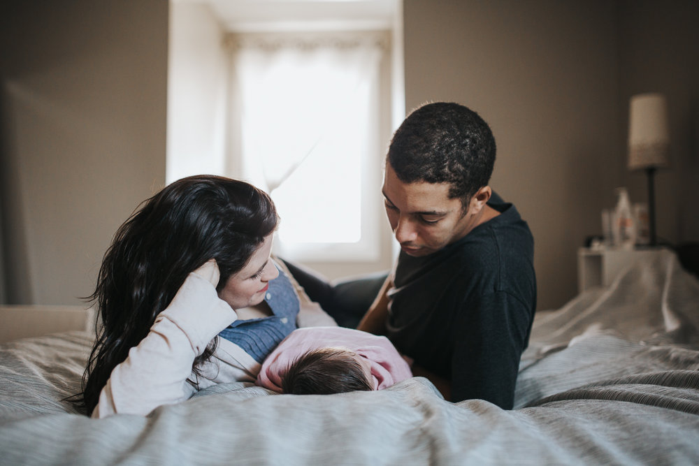husband and wife lie on bed with 2 week old baby girl between them - Stouffville in-home photography session