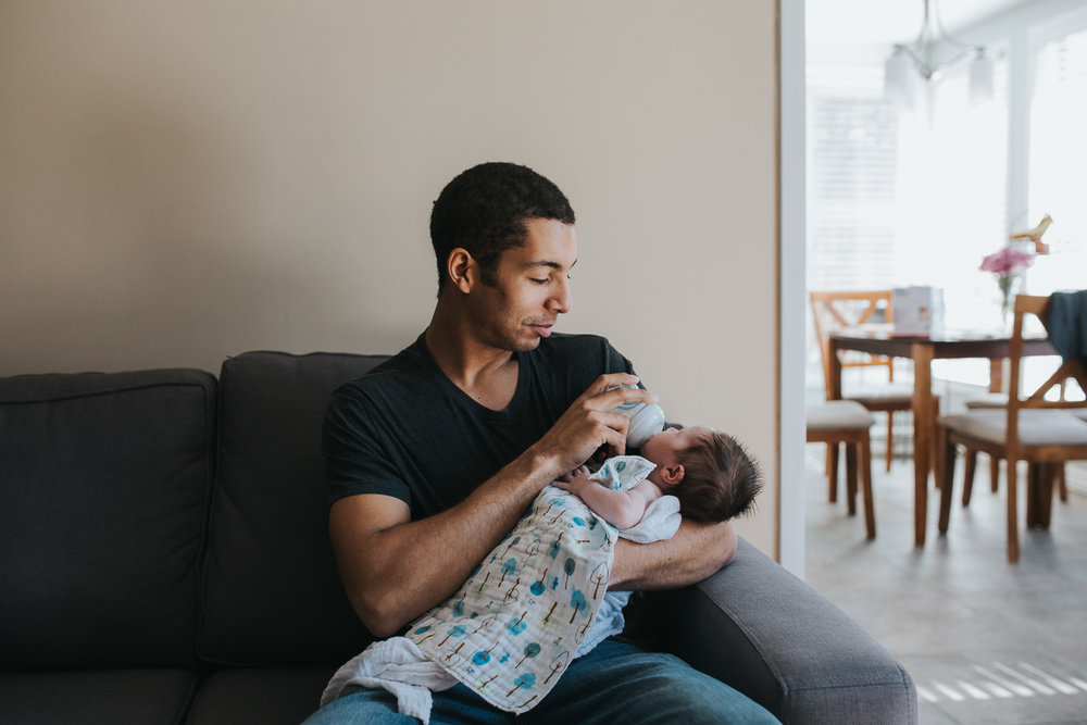 new dad holding 2 week old baby girl and feeding her bottle on couch - Newmarket lifestyle photos