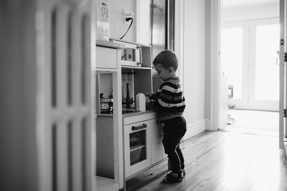 3 year old toddler boy plays with toy kitchen - Barrie in-home photography