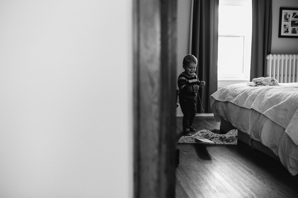3 year old toddler boy pulling toy plane around in parent's bedroom - Stouffville lifestyle photography