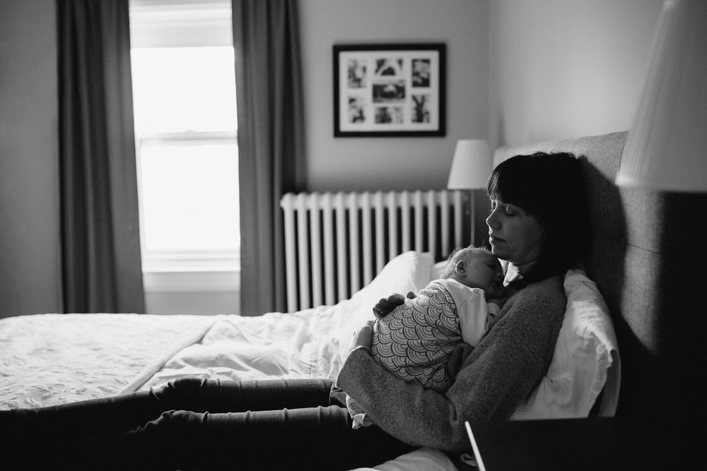 mom sits on master bed holding 5 week old baby daughter to her chest, eyes closed - Barrie lifestyle photography