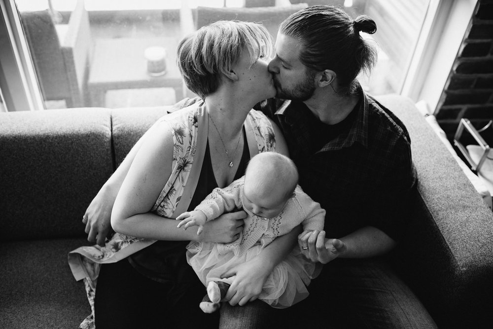 family of 3 sitting on couch, husband and wife kissing with 5 month old baby girl between them - Newmarket lifestyle photos