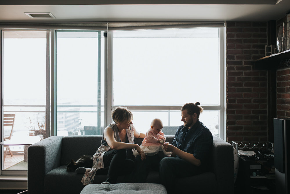 family of 3 sitting on couch in front of window as parents play with 5 month old baby girl - Barrie in-home photos