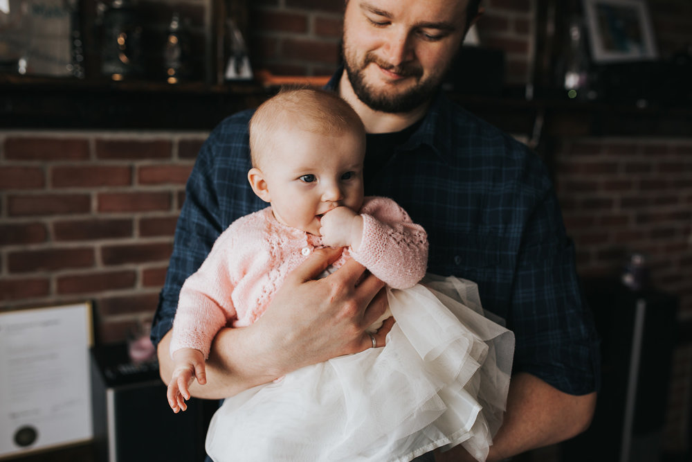 dad holds 5 month old baby girl in pink sweater who is chewing on her hands - Barrie lifestyle photography