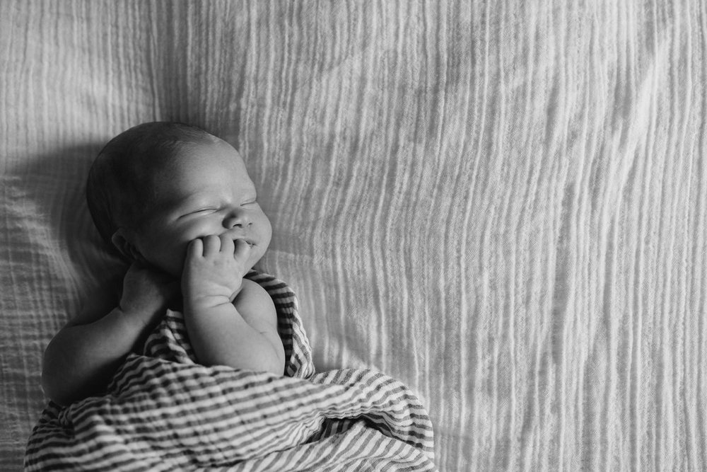 2 week old baby boy asleep, lying on bed in striped neutral swaddle with hand in mouth - Stouffville lifestyle photography