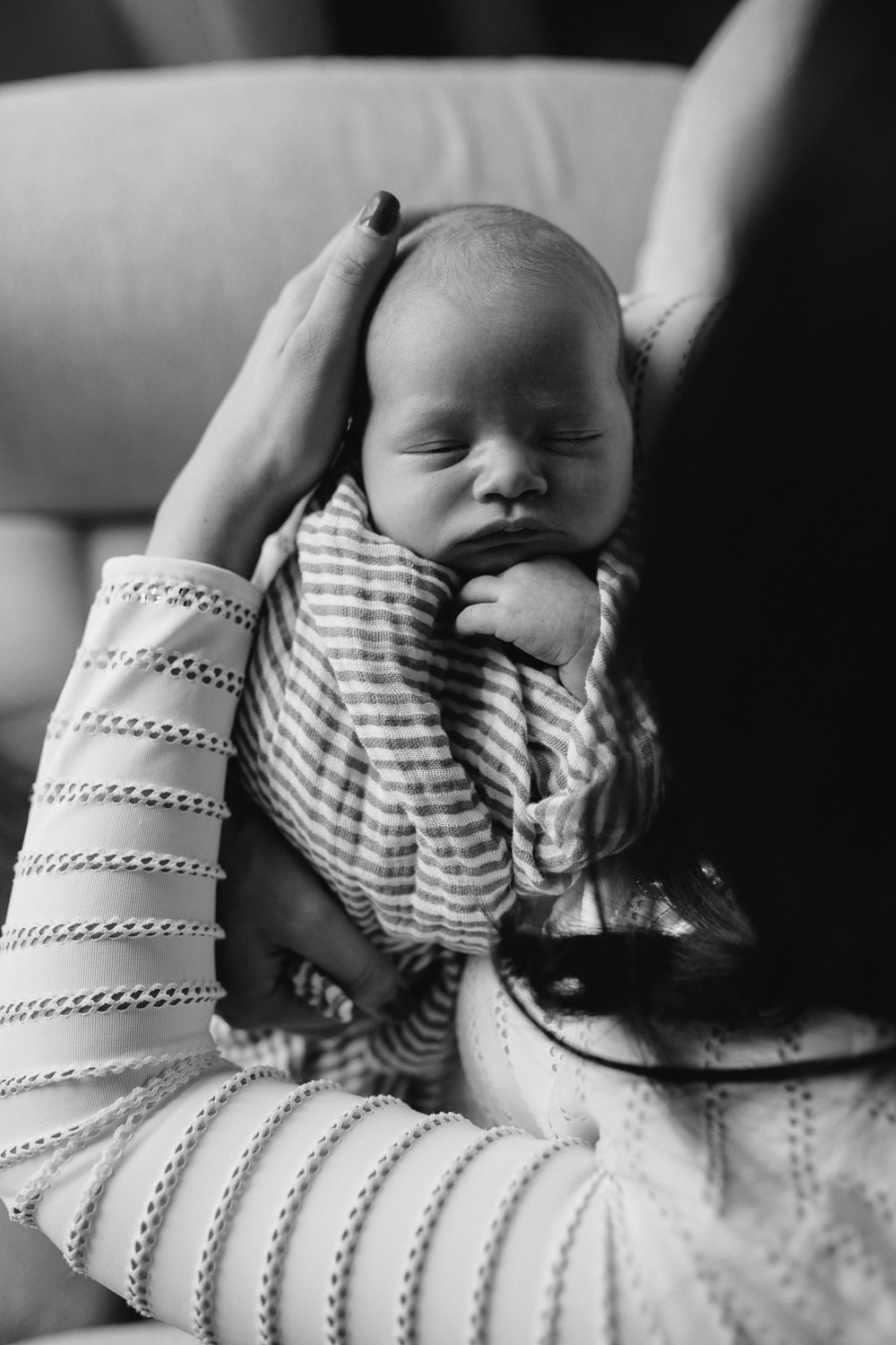 2 week old baby boy asleep with hand under chin, lying on mother's arms - Newmarket lifestyle photography
