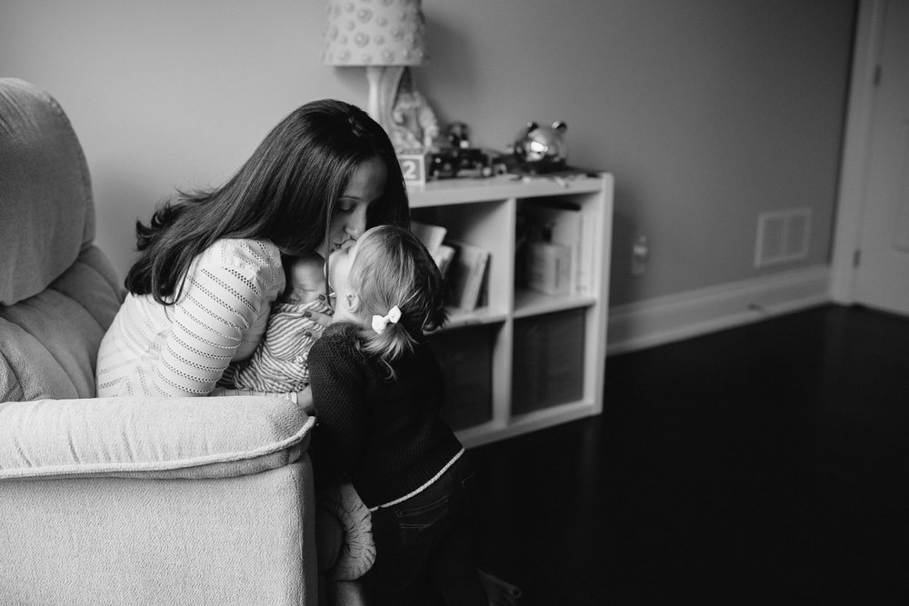 mom sitting in chair holding 2 week old baby boy, leaning over to kiss 2 year old toddler daughter - Stouffville in-home photography