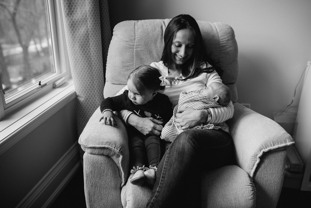 mom sitting in glider holding 2 year old toddler daughter and 2 week old baby son - Markham in-home photography