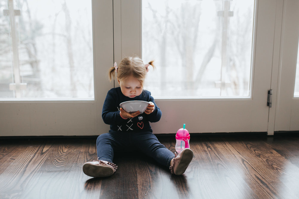 2 year old toddler girl with pigtails sitting on floor eating snack from a bowl - Newmarket lifestyle photos