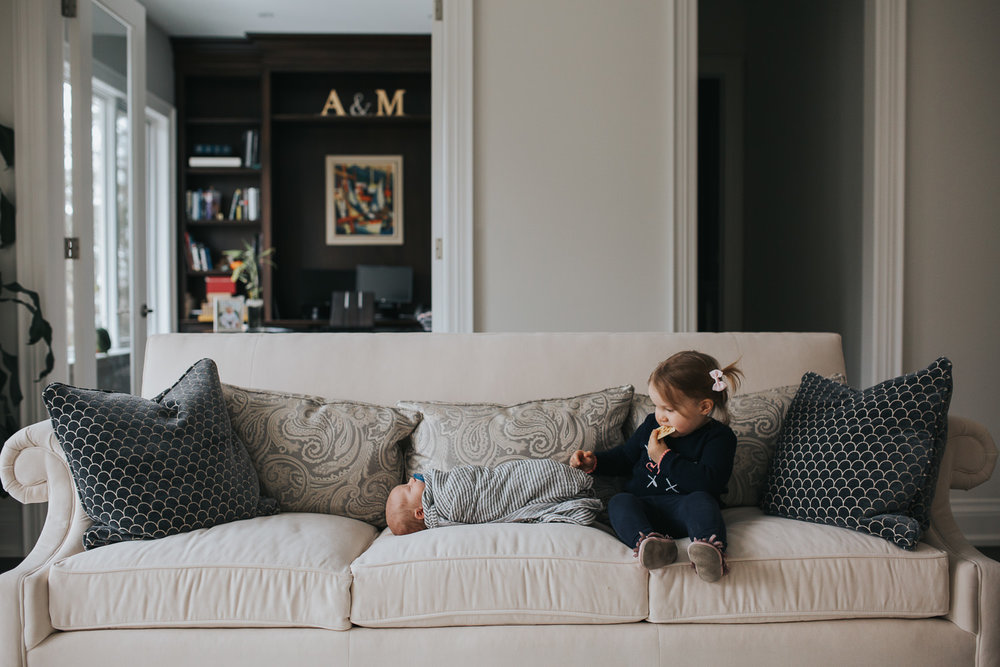 2 year old toddler girl sits on couch, looking at 2 week old baby brother next to her - Barrie in-home photos