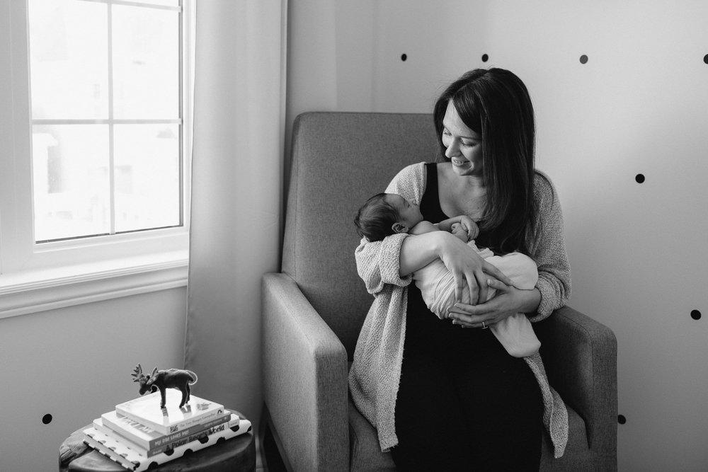 new mom sitting in rocking chair holding 2 week old baby boy, looking at him - Markham Lifestyle Photography