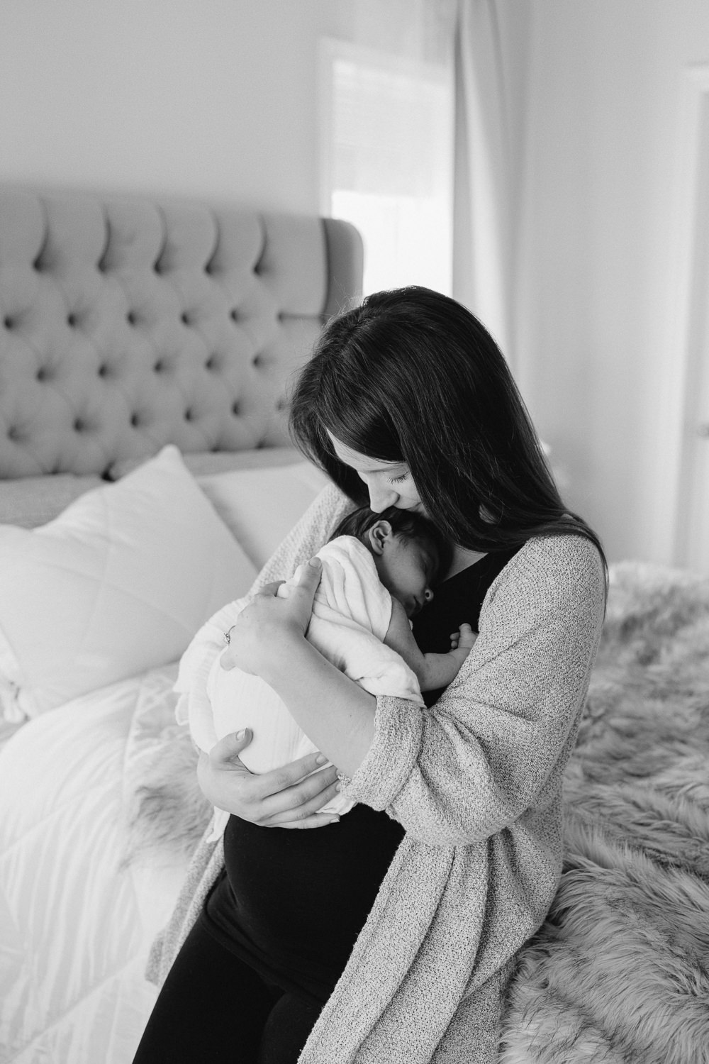 mom snuggling 2 week old baby boy to chest, kissing his forehead - Newmarket in-home photography