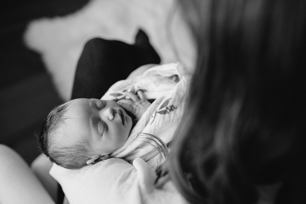 new mom sits in chair holding swaddled, sleeping 2 week old baby girl - Barrie In-Home Photography