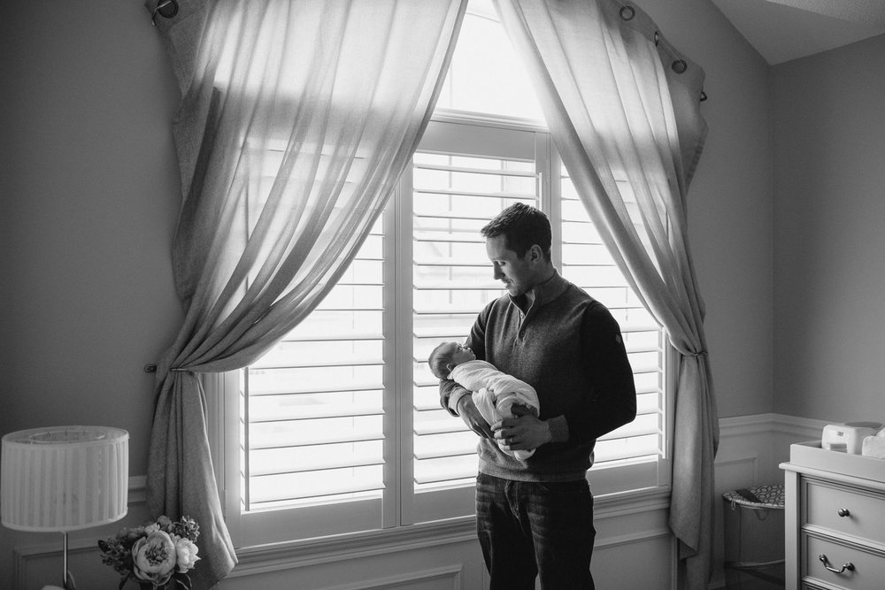 first time father standing in front of nursery window holding and looking at 2 week old baby daughter - Markham Lifestyle Photography