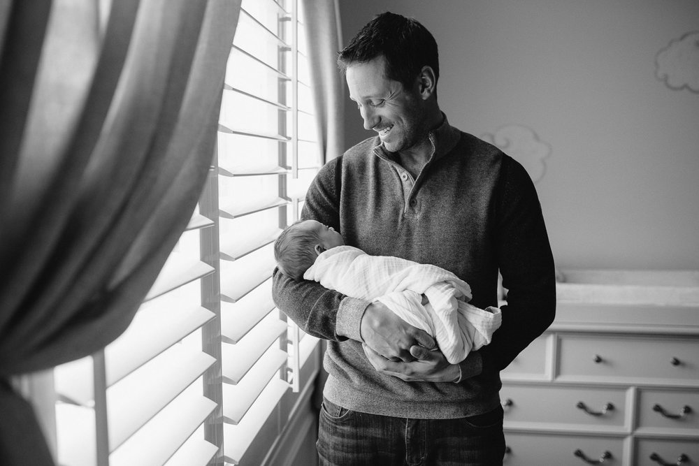 new dad standing in front of nursery window holding and looking at 2 week old baby daughter - Uxbridge Lifestyle Photography