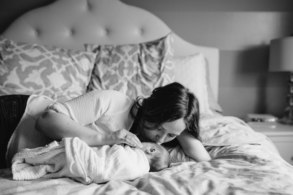 first time mom lying on master bed with 2 week old baby daughter, kissing her on forehead - Markham Lifestyle Photos