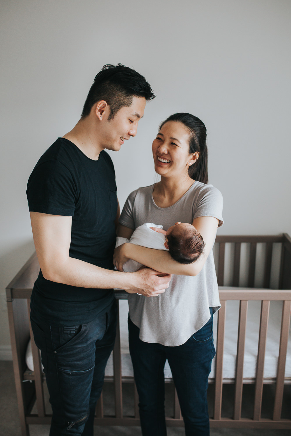 New parents laughing and holding 2 week old baby son in nursery - Stouffville Lifestyle Photos