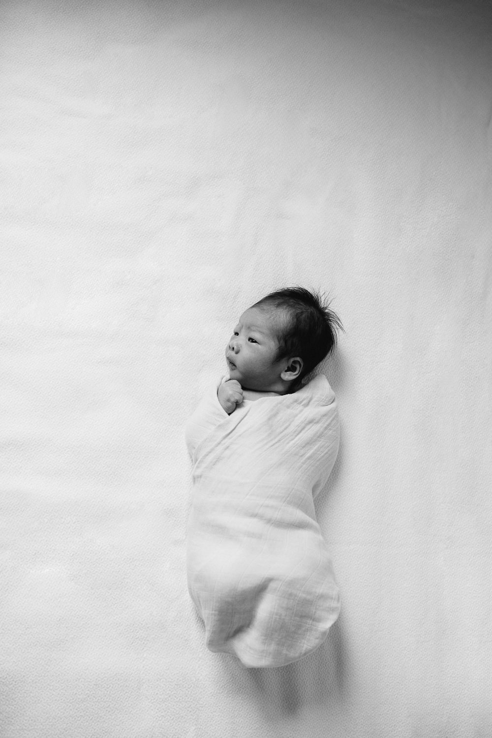 2 week old baby boy with dark hair wrapped in swaddle lying awake on bed - Barrie Lifestyle Photography