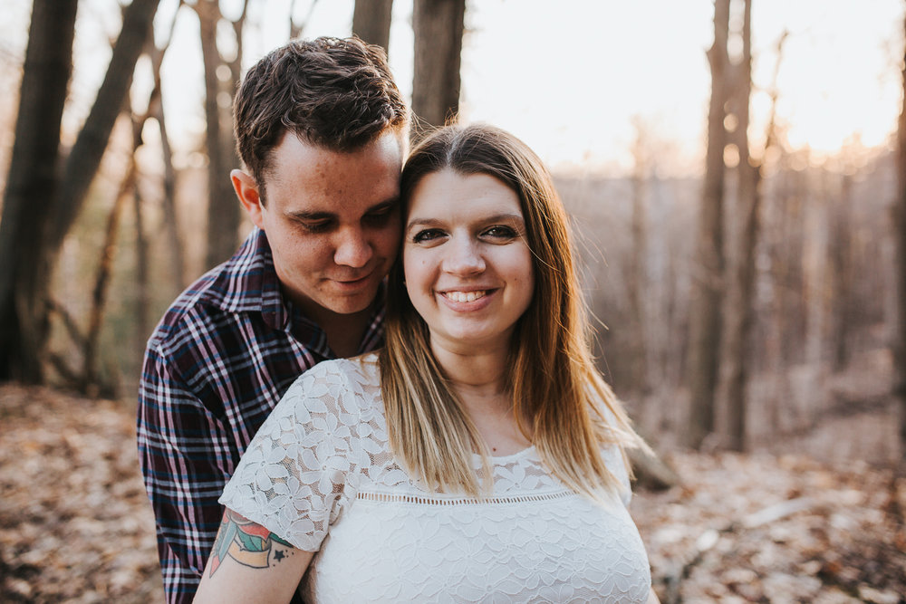 husband embraces pregnant wife, standing in forest with sunset behind them - Barrie Lifestyle Photos