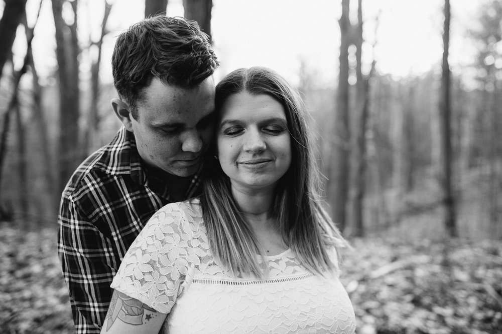 husband embraces pregnant wife, standing in forest with sunset behind them - Uxbridge Lifestyle Photos
