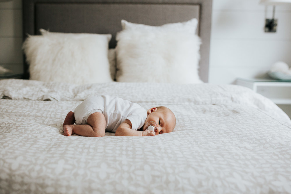two week old baby boy lying on tummy on bed wearing white onesie - Markham In-Home Photography
