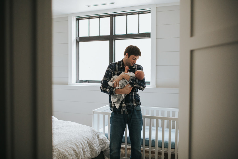 new dad holds 2 week old baby son in front of crib - Barrie In-Home Photography
