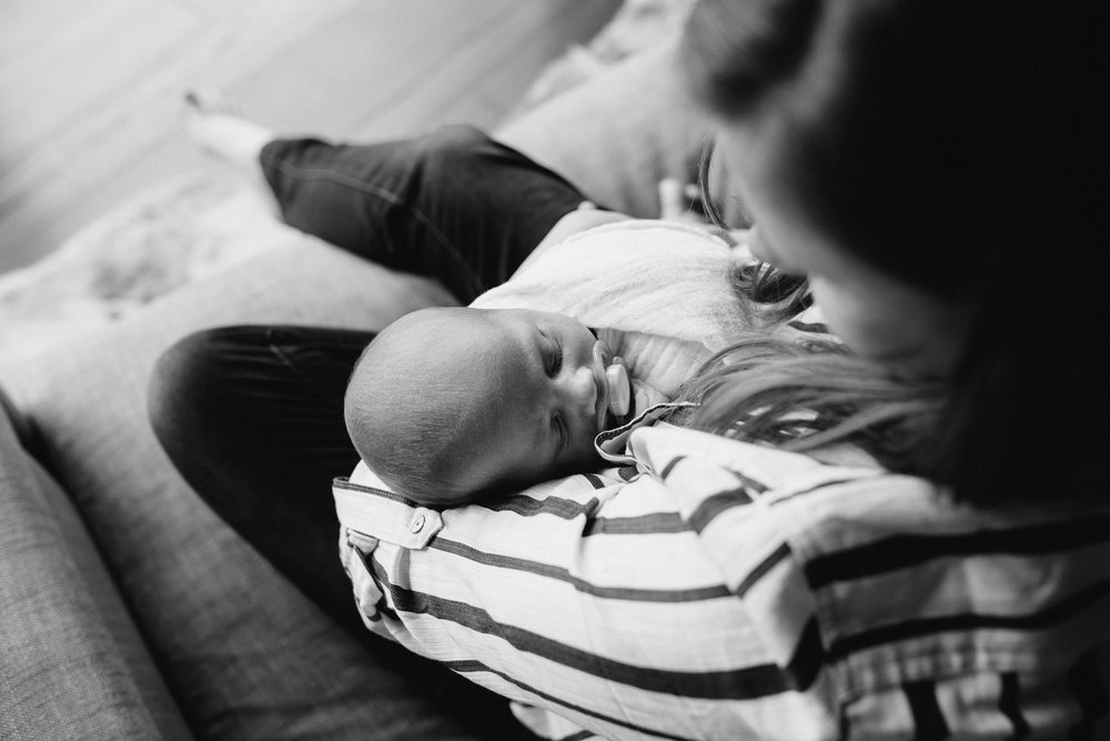 first time mother sitting in chair holding swaddled 2 week old baby boy - Newmarket In-Home Photography