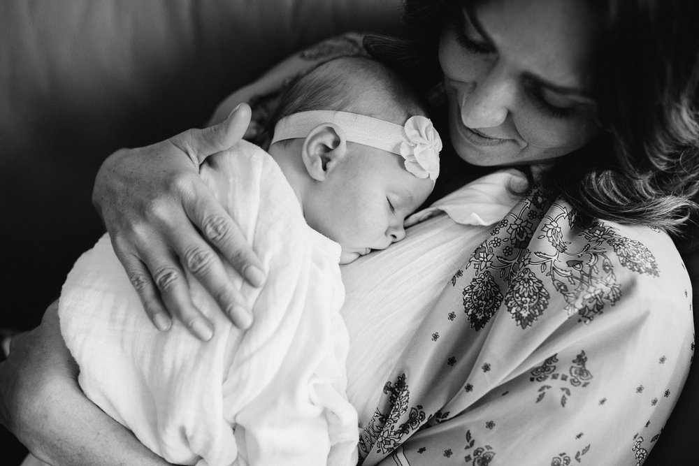 first time mom snuggling 2 month old sleeping baby daughter on chest - Markham Lifestyle Photography