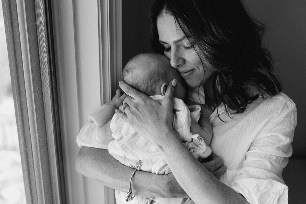first time mother with eyes close snuggling 2 month old baby girl to chest - Barrie Lifestyle Photography