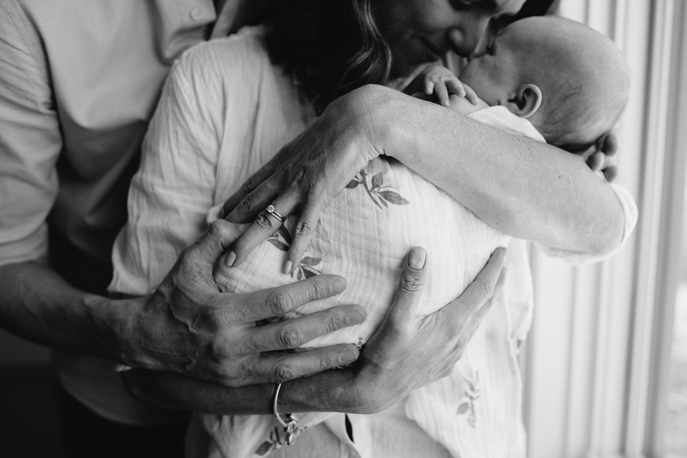 new parents stand at window, mom holding 2 month old daughter, dad embraces mom - Markham In-Home Photography