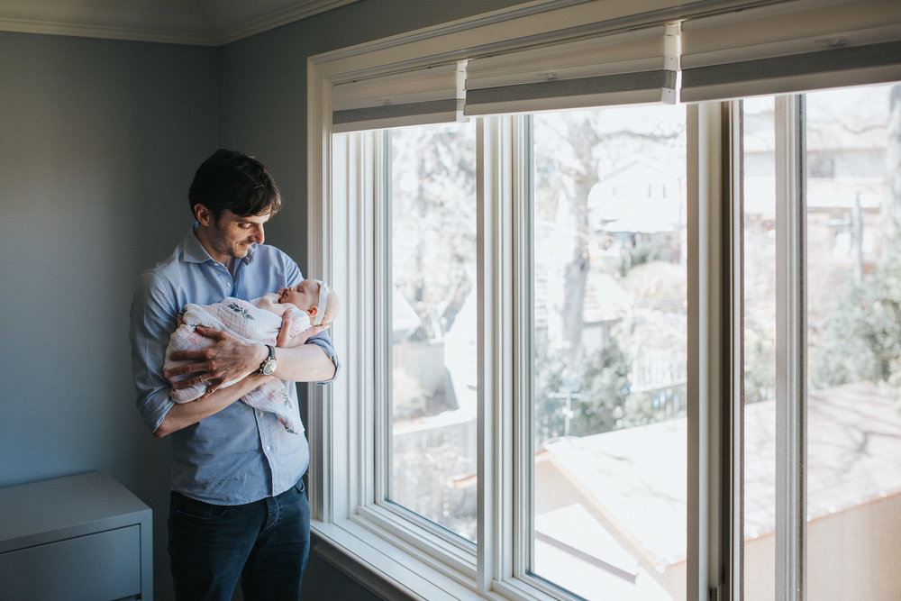new father standing at window holding 2 month old baby girl in arms - Barrie In-Home Photography