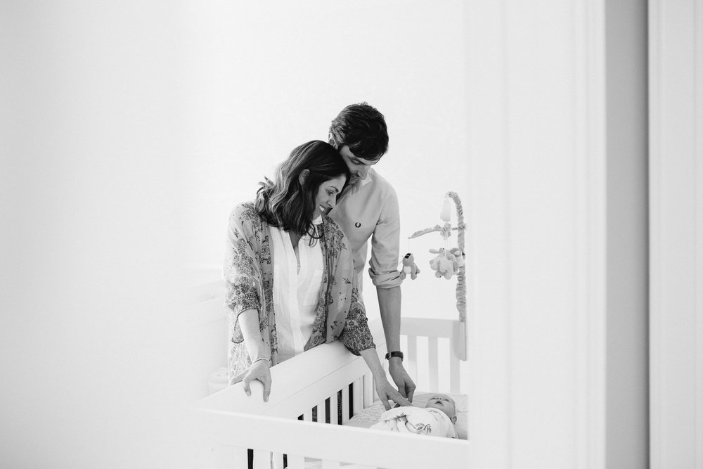 husband and wife stand in nursery looking into crib at 2 month old baby girl - Stouffville Lifestyle Photos