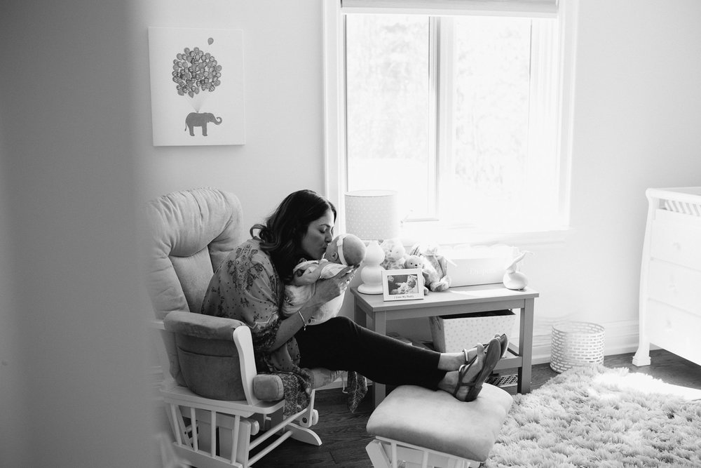 new mom sitting in nursery glider kissing 2 month old baby daughter's face - Markham Lifestyle Photos