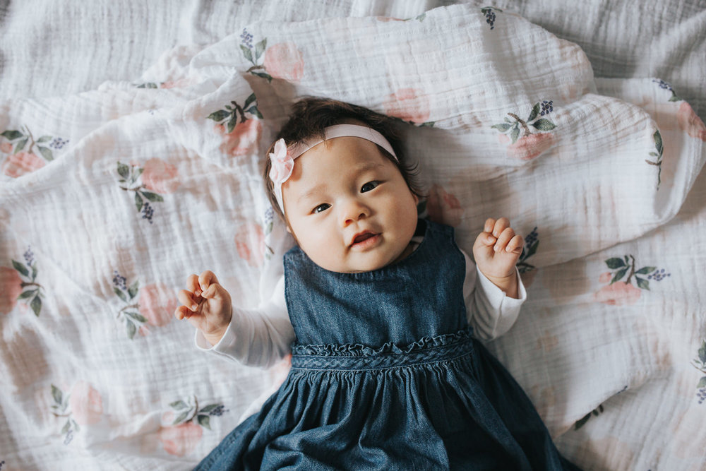 3 month old baby girl in blue dress lying on floral blanket looking at camera - Newmarket Lifestyle Photography