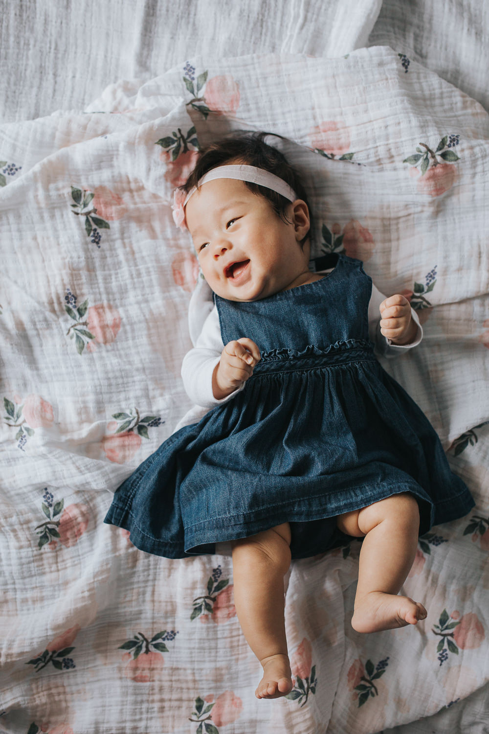 3 month old baby girl in blue dress and pink headband lying on floral blanket laughing -Markham Lifestyle Photography