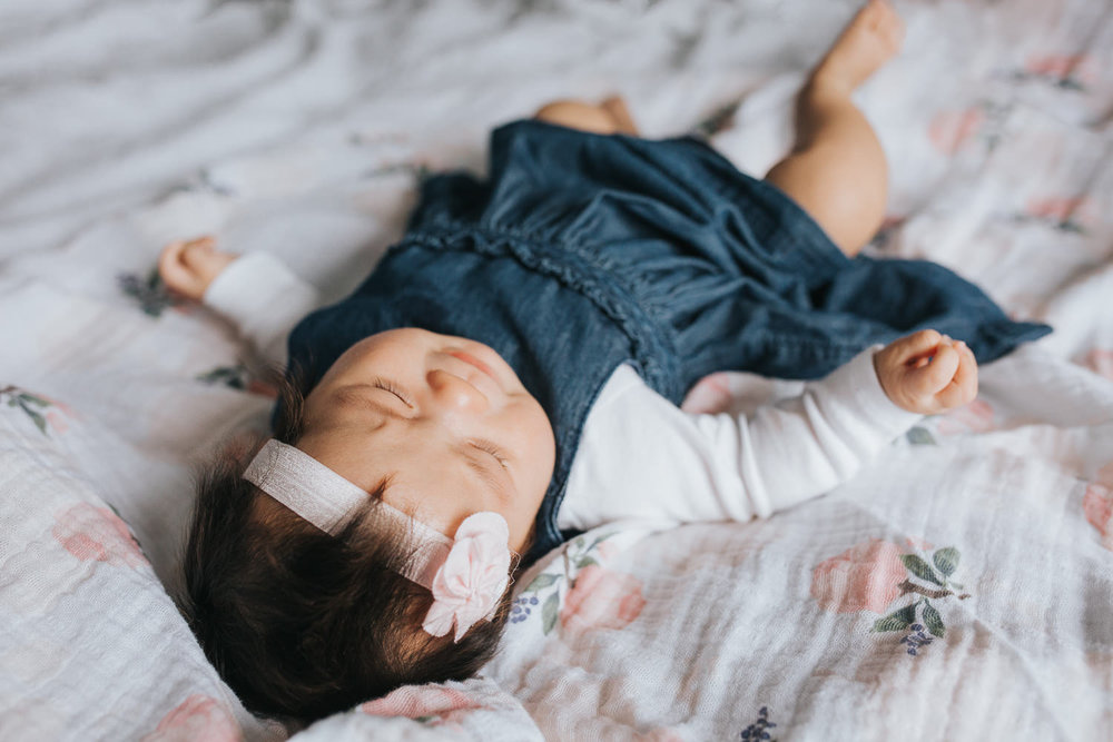 3 month old baby girl in blue dress lying on floral blanket -Barrie Lifestyle Photography
