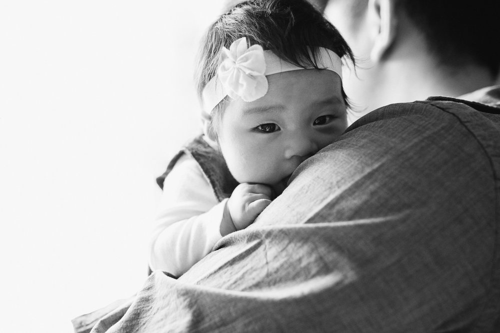 3 month old baby girl looking at camera over dad's shoulder - Uxbridge Lifestyle Photography