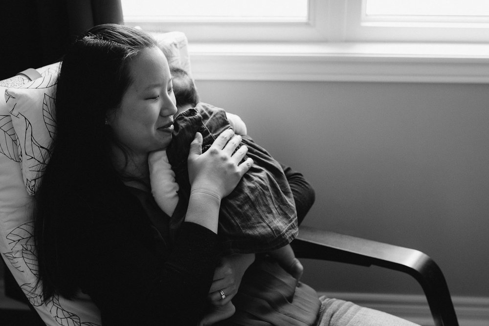 new mom snuggles 2 month old baby daughter to chest - Newmarket In-Home Photography