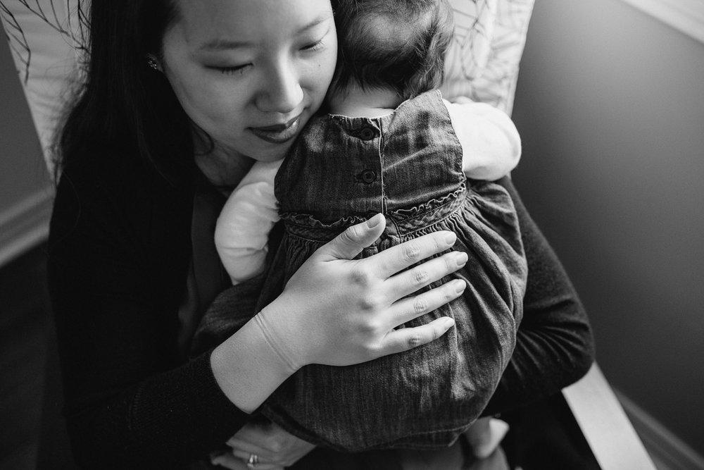 new mom snuggles 2 month old baby daughter to chest - Markham In-Home Photography