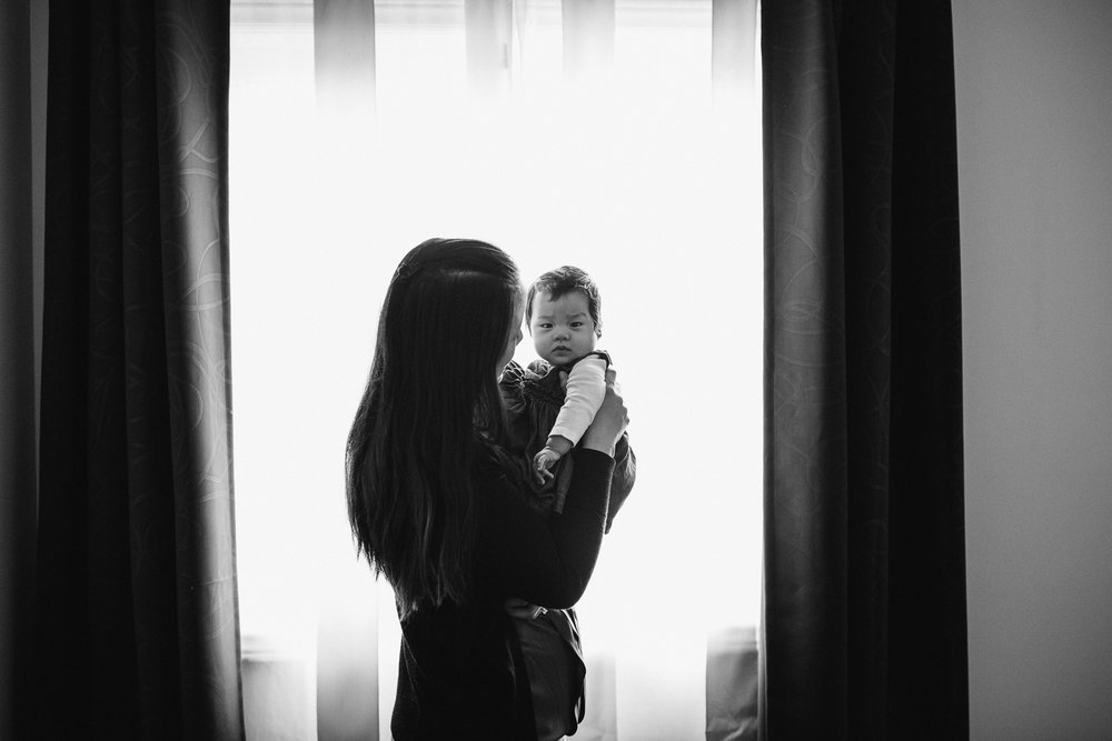 first time mom standing on front of window holding 3 month old baby daughter - Uxbridge In-Home Photography