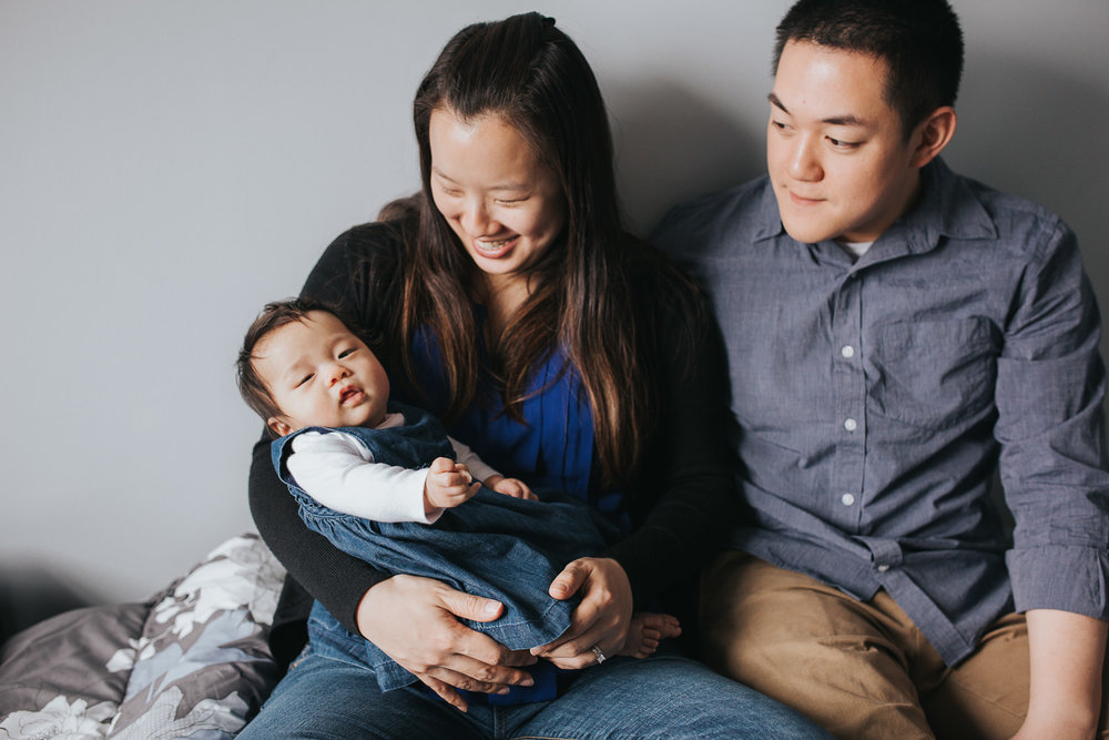 new parents sitting on master bed holding and looking at 3 month old baby girl - Barrie Lifestyle Photos