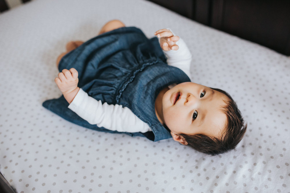 3 month old baby girl in blue dress lying in nursery crib, looking at camera - Markham Lifestyle Photography